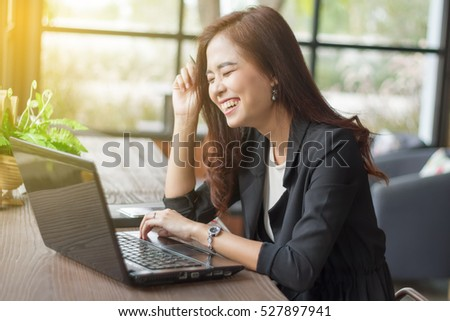 Asian business women using notebook and business women smiling happy for working ,soft focus