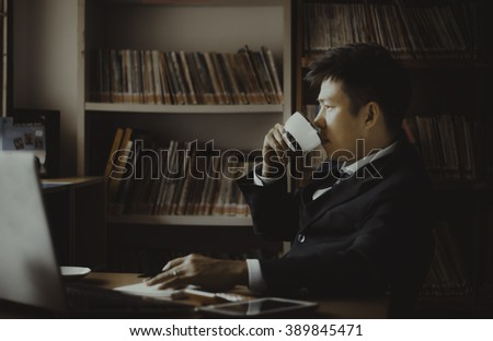 Asian businesses bring a cup of coffee and looking into the dist - stock photo