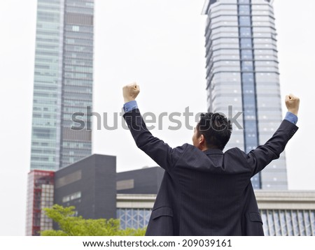 asian businessman celebrating with arms raised. - stock photo