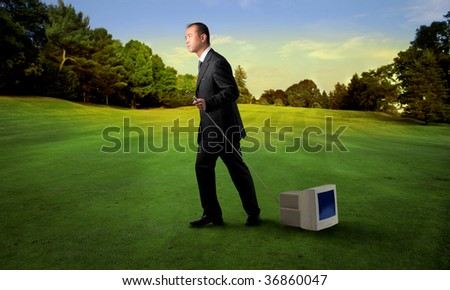 asian businessman dragging an old computer in a park - stock photo