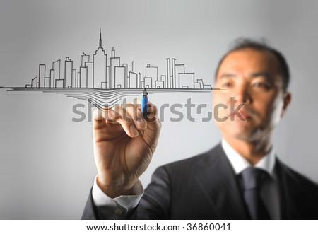 asian businessman drawing a modern city - stock photo