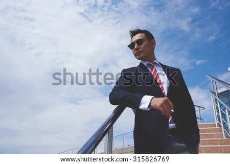 Asian businessman dressed in elegant suit standing outdoors against blue sky with copy space for your advertising content, young men entrepreneur smoking a cigarette in the fresh air during work break - stock photo