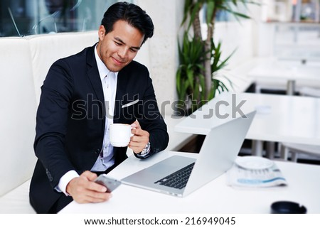 Asian businessman drinking coffee while working in a cafe,happy and handsome businessman with cup of coffee looking at his mobile phone during a work break outdoors in cafe,businessman at the notebook - stock photo