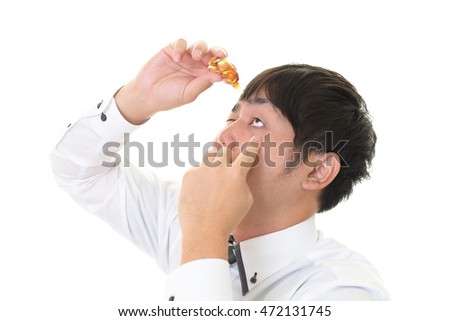 Asian businessman dripping eye with eyes drops.