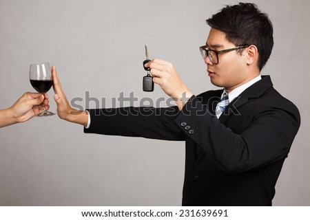 Asian businessman drive not drink , say no to wine with car key in hand on gray background - stock photo