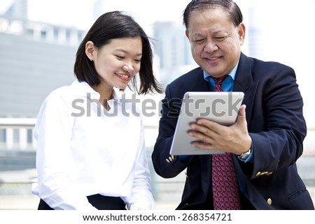 Asian businessman & female executive using tablet - stock photo