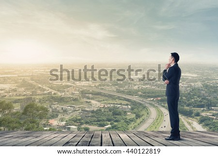Asian businessman has a plan, copyspace on sky. - stock photo