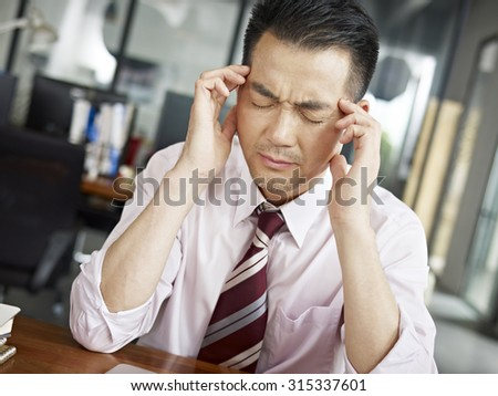 asian businessman having a headache in office. - stock photo