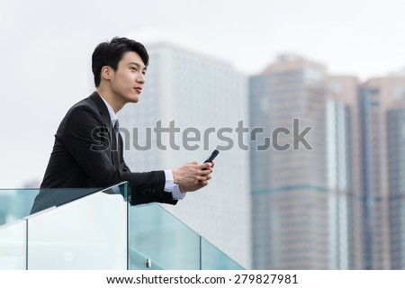 Asian businessman holding with cellphone - stock photo