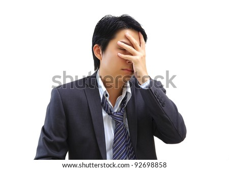 Asian businessman holds his hand to his face - stock photo