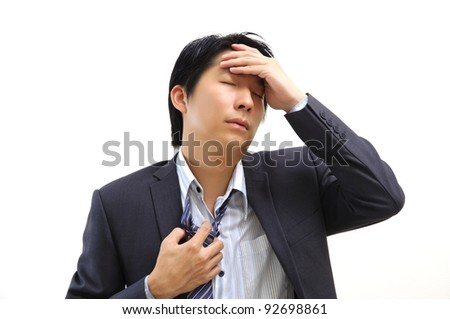 Asian businessman holds his hand to his head - stock photo
