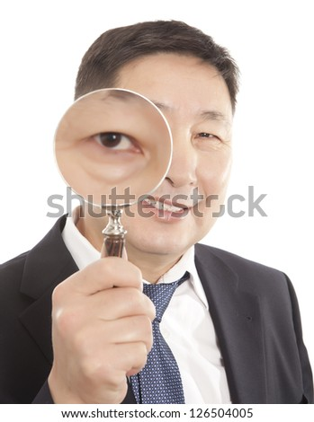 Asian businessman in a suit looking through a magnifying glass. Isolated on white background - stock photo