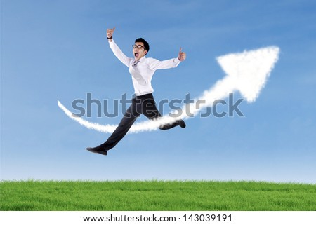 Asian businessman is jumping over up arrow sign cloud at the green field - stock photo