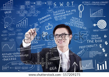 Asian businessman is writing success concept on transparent whiteboard - stock photo