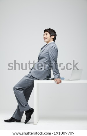 Asian businessman leaning on desk with laptop