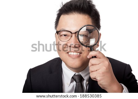 Asian businessman look through magnifying glass and smile