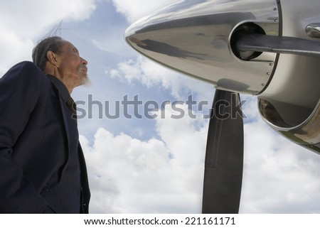 Asian businessman looking at airplane - stock photo