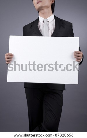 Asian businessman looking cool holding an empty white board
