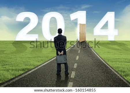 Asian businessman looking into the future in 2014 outdoor - stock photo