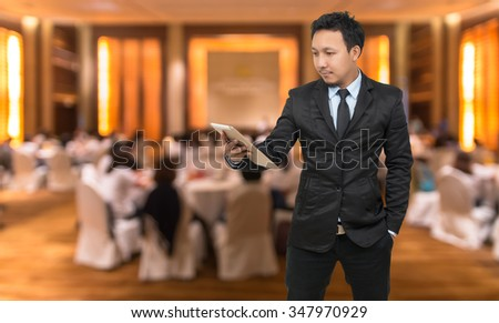 Asian Businessman looking the tablet on Abstract blurred photo of conference hall or seminar room with attendee background, business concept - stock photo