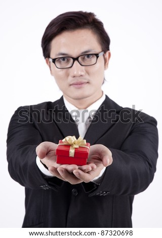 Asian businessman offering a gift isolated on white - stock photo