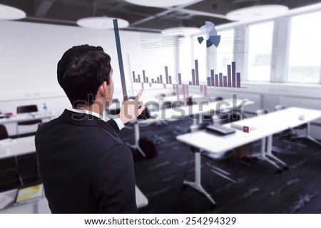 Asian businessman pointing against classroom - stock photo