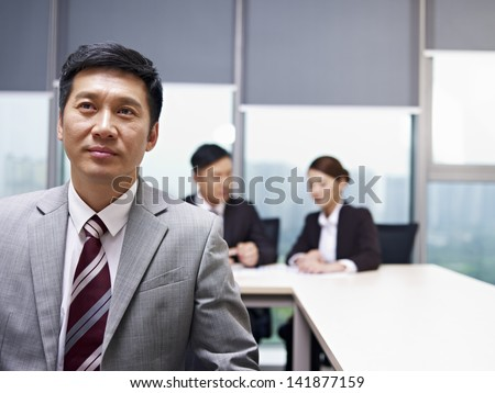 asian businessman praying for help in office - stock photo