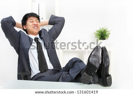Asian businessman relaxing with his feet up on top of his desk and his hands clasped behind his head smiling happily to himself - stock photo