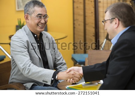 Asian businessman Shake hands with foreigners - stock photo