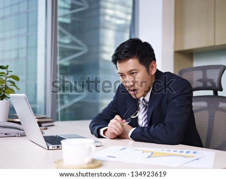 asian businessman sitting and thinking in office. - stock photo