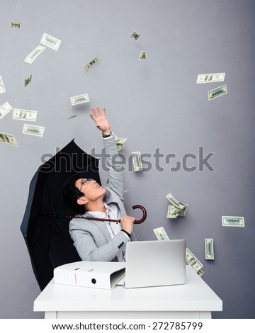 Asian businessman sitting at the table with umbrella with rain of money over gray background - stock photo