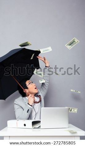 Asian businessman sitting at the table with umbrella with rain of money over gray background. Looking up - stock photo