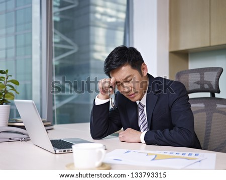 asian businessman sitting in office, looking tired.