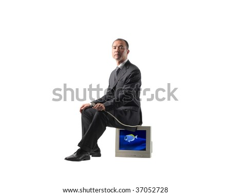 asian businessman sitting on a pc screen - stock photo