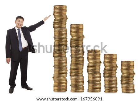 Asian businessman standing next to gold coins  - stock photo
