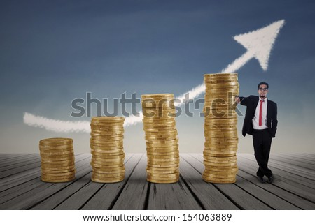 Asian businessman standing next to gold coins chart with blue sky background - stock photo