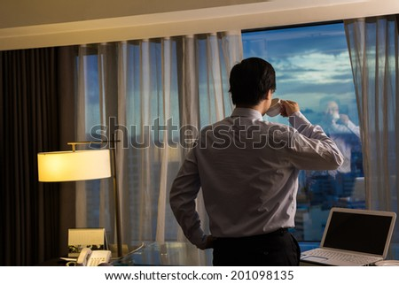 Asian businessman take a cup of coffee and looking into the distance, concept of traveling business, dream, work at night etc. - stock photo