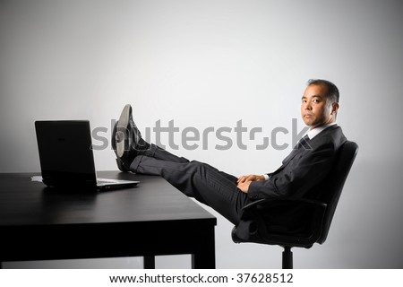 asian businessman taking a break in his office - stock photo