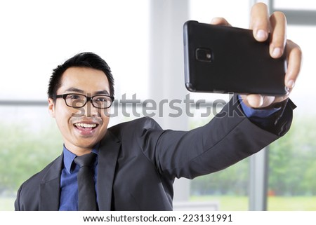 Asian businessman taking self portrait with smartphone in office - stock photo