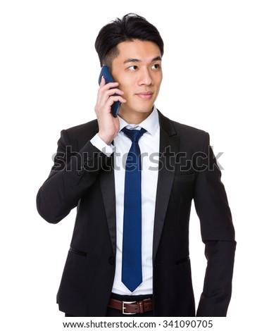 Asian Businessman talk to smart phone - stock photo