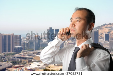asian businessman talking at the mobile phone against a city view - stock photo