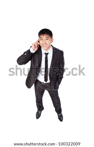 Asian businessman talking mobile cell phone, happy smile looking up, using cellphone, top view full length portrait of young business man phone call, wear elegant suit isolated over white background - stock photo