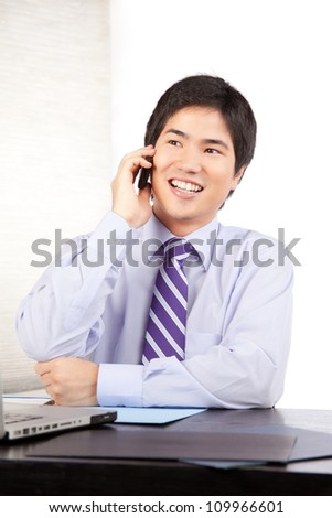 Asian businessman talking on cell phone at work . - stock photo