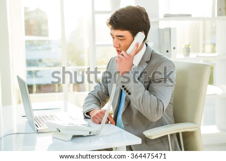 Asian businessman talking on the telephone in his office - stock photo