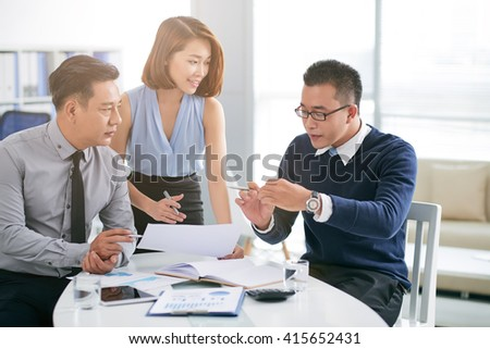 Asian businessman talking to coworkers about his project - stock photo