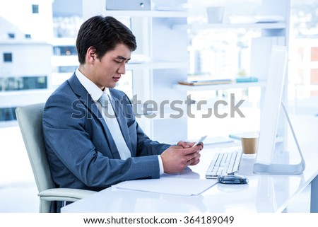 Asian businessman using his phone in his office