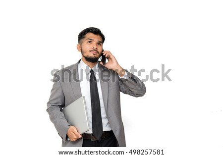 Asian businessman using smartphone while holding laptop isolated on white background