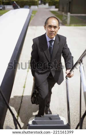 Asian businessman walking up airplane steps