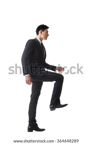 Asian businessman walking up on stairs, full length portrait isolated