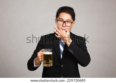 Asian businessman with beer whistle with fingers on gray background - stock photo
